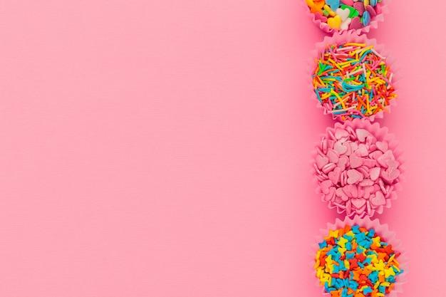 Chispitas de azúcar, pastel de decoración y helados y galletas en rosa