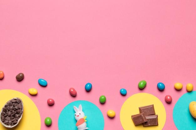 Choco chips; estatua de conejo; trozos de chocolate y caramelos de colores sobre fondo rosa con espacio para texto