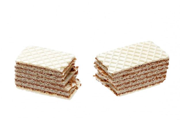 El chocolate aislado agrietó las obleas crujientes con las migas en el fondo blanco