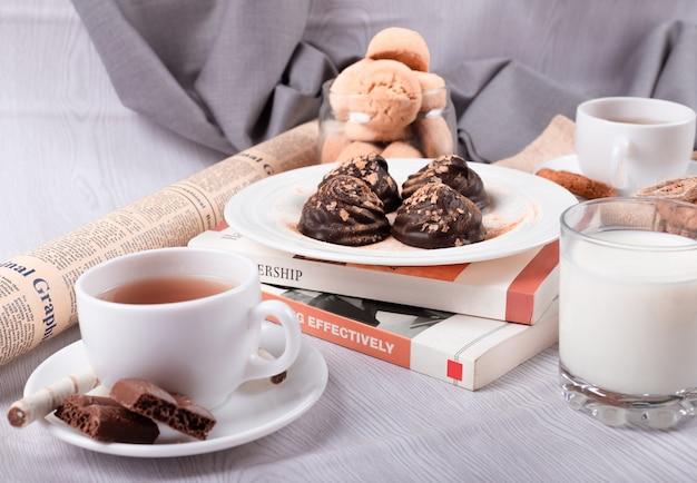 Chocolate, bocadillos dulces y té sobre la mesa.