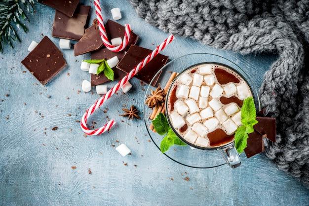 Chocolate caliente casero con menta, bastón de caramelo y malvavisco, mesa azul claro con una manta cálida,