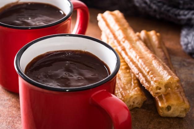 Chocolate caliente con churros en la mesa de madera de cerca