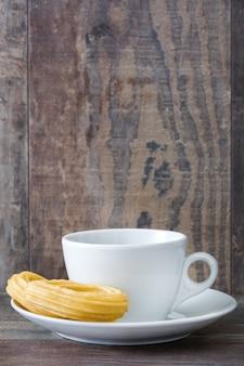 Chocolate caliente con churros en mesa de madera desayuno español