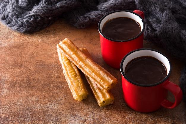 Chocolate caliente con churros sobre superficie oxidada