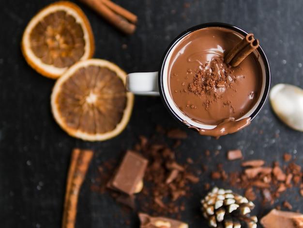 Chocolate caliente junto a naranjas y dulces de cacao.