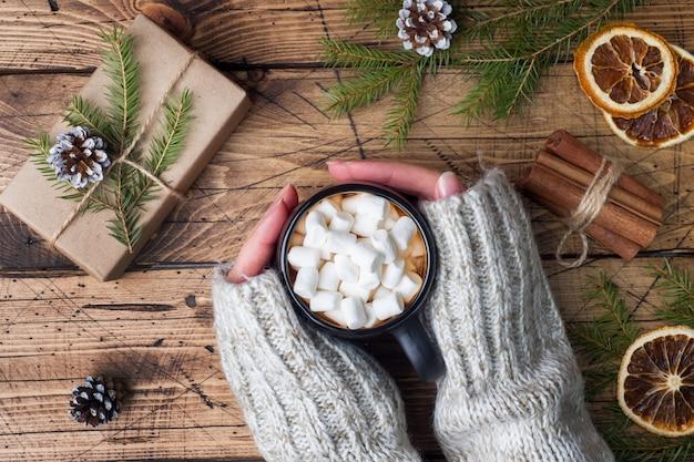 Chocolate caliente con malvavisco, sostenga las manos femeninas con canela, anís, nueces sobre madera