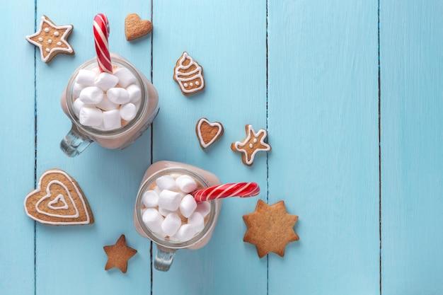 Chocolate caliente con malvaviscos, una caña de azúcar y galletas de jengibre sobre un fondo turquesa.