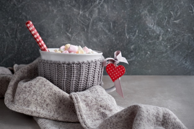 Chocolate caliente con malvaviscos, corazón rojo en la taza, espacio de copia