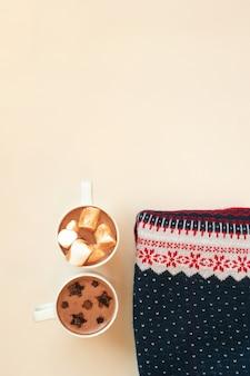 Chocolate caliente con malvaviscos y decoración de cacao en polvo en forma de estrellas en tazas blancas y suéter de navidad