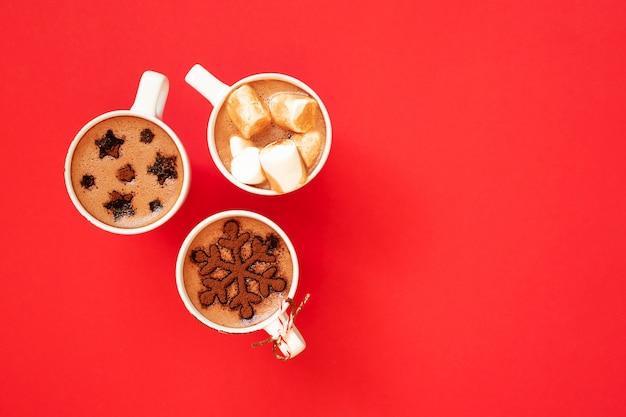 Chocolate caliente con malvaviscos y decoración de cacao en polvo en tazas blancas sobre rojo