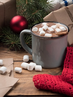 Chocolate caliente con malvaviscos y decoración navideña en una mesa de madera. copie el espacio.