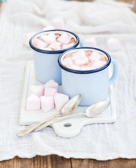 Chocolate caliente y malvaviscos en forma de corazón en tazas antiguas de esmalte en una tabla de servir de cerámica blanca