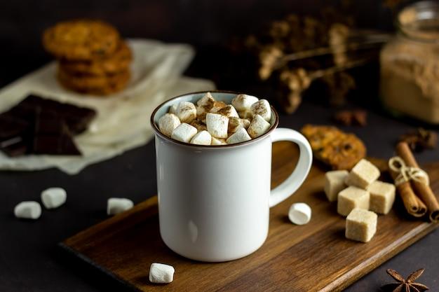 Chocolate caliente con malvaviscos en una taza blanca sobre un oxidado