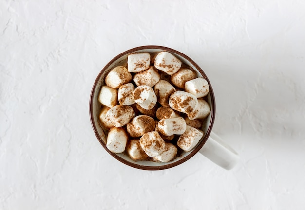 Chocolate caliente con malvaviscos en una taza blanca