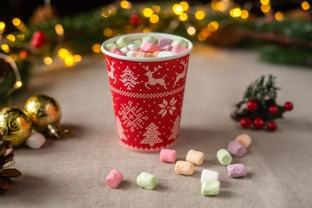 Chocolate caliente con malvaviscos en una taza de papel navideña