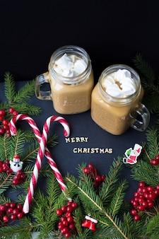 Chocolate caliente y marshmellou del caramelo en el fondo de árboles. la inscripción feliz navidad