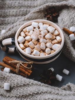 Chocolate caliente o cacao con malvaviscos en una taza de canela. bufanda de punto caliente