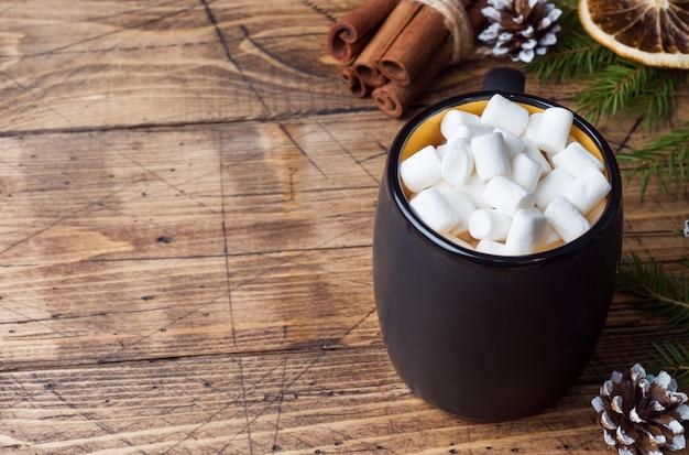 Chocolate caliente con palitos de canela y malvavisco, anís, nueces sobre madera