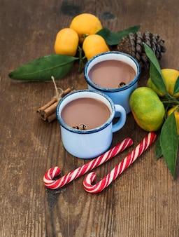 Chocolate caliente en tazas de metal esmaltado, mandarinas frescas, palitos de canela, piña y bastones de caramelo sobre madera rústica
