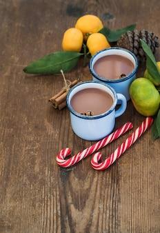 Chocolate caliente en tazas de metal esmaltado, mandarinas frescas, palitos de canela, piña y bastones de caramelo sobre una mesa de madera rústica