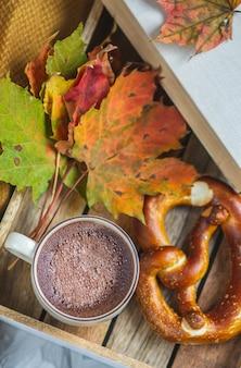 Chocolate caliente tiempo otoño panadería manta pretzel hojas amarillas sobre fondo
