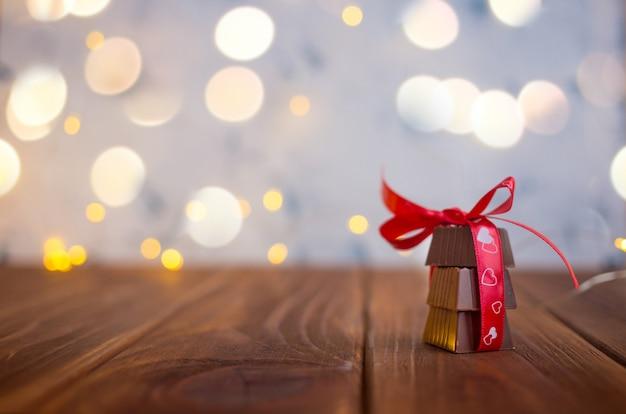 Chocolate con cinta y corazón en el día de san valentín y bokeh.