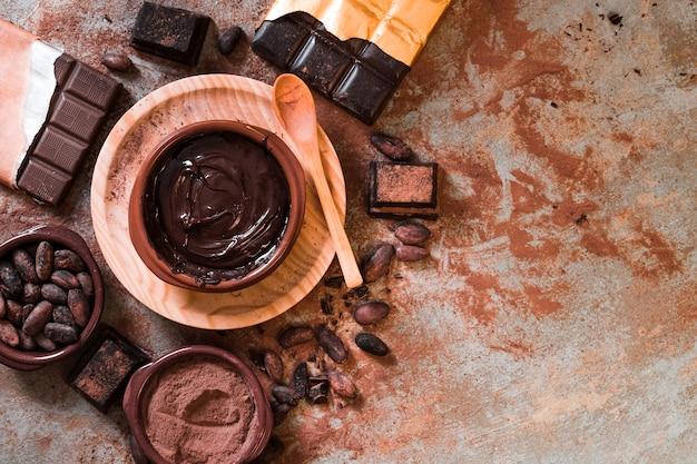 Chocolate derretido y barra de chocolate hecha con granos de cacao en la mesa