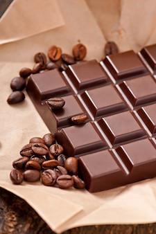 Chocolate y granos de café sobre papel beige.