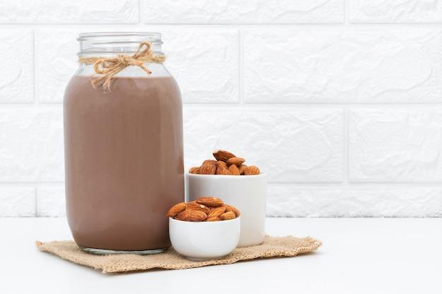 Chocolate con leche y almendras en un vaso sobre blanco