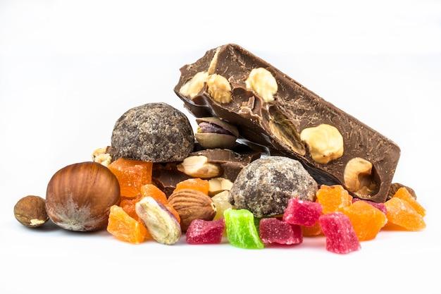Chocolate con leche, avellana y nuez de almendra, frutas confitadas aisladas sobre fondo blanco.