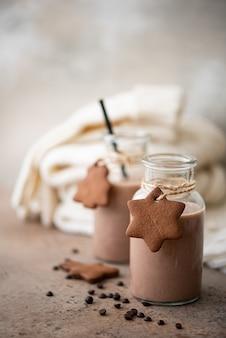 Chocolate con leche con galletas y cálida bufanda tejida sobre la mesa