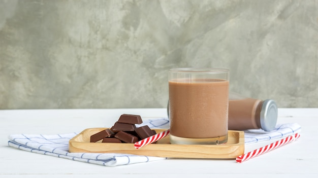 Chocolate con leche en una mesa de madera blanca.