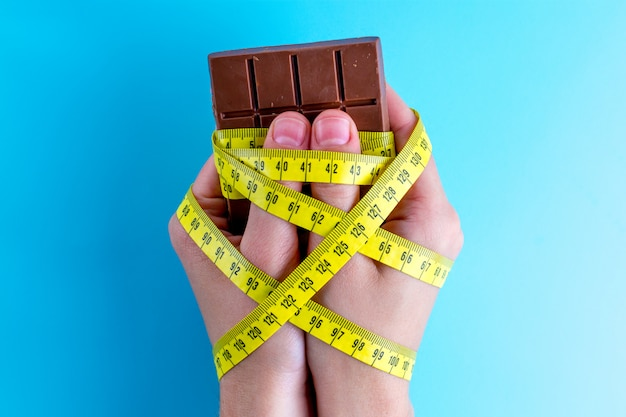 Chocolate en las manos atadas con cinta métrica amarilla