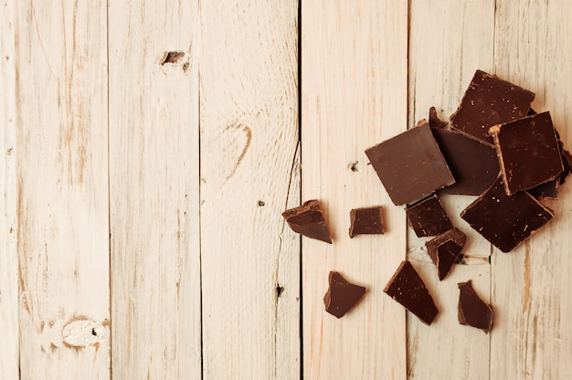 Chocolate negro sin azúcar y sin gluten para diabéticos y alérgicos. el chocolate negro roto en pedazos descansa sobre una mesa blanca en un estilo rústico.