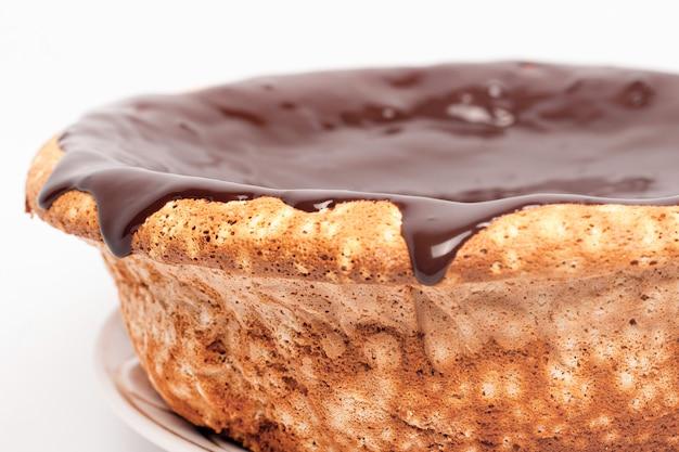 Chocolate que fluye a los lados del pastel. bizcocho con caramelo vertiendo alrededor de los bordes sobre fondo blanco de cerca.