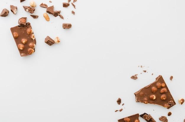 Chocolate roto dispersado de la nuez en el fondo blanco