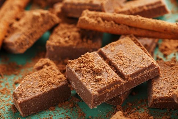 Chocolate roto en rodajas con cacao en polvo y especias sobre una superficie verde
