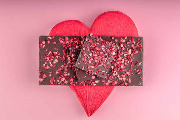 Chocolate con trozos de bayas secas se encuentra una pila de corazón rojo