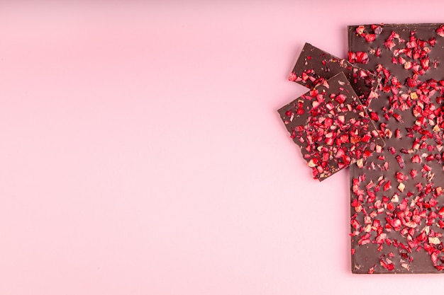 Chocolate con trozos de fresas secas se encuentra una pila sobre fondo rosa