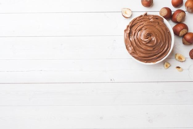 Chocolate de la tuerca del turrón en una placa en un fondo blanco con las nueces de la avellana.