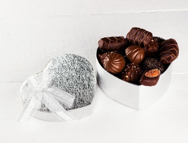Chocolates en una caja en forma de corazón sobre un fondo blanco.