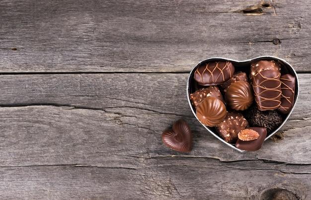 Chocolates en una caja en forma de corazón sobre un fondo oscuro