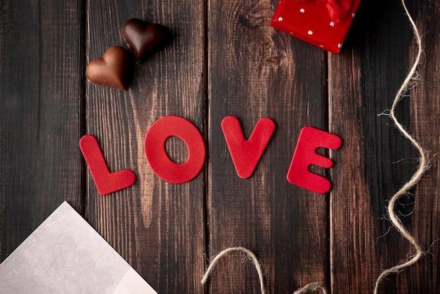 Chocolates en forma de corazón sobre fondo de madera con amor