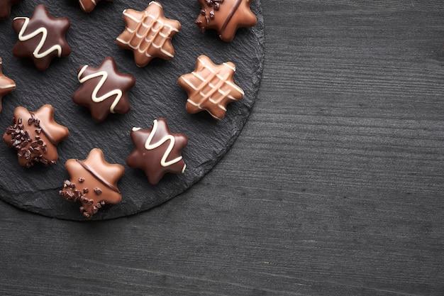 Chocolates en forma de estrella sobre fondo oscuro con textura, espacio de copia