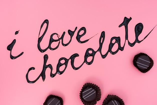 Chocolates sobre fondo rosa con jarabe de chocolate escrito