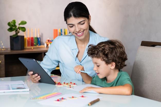 Chold estudiando desde casa con la ayuda de la madre