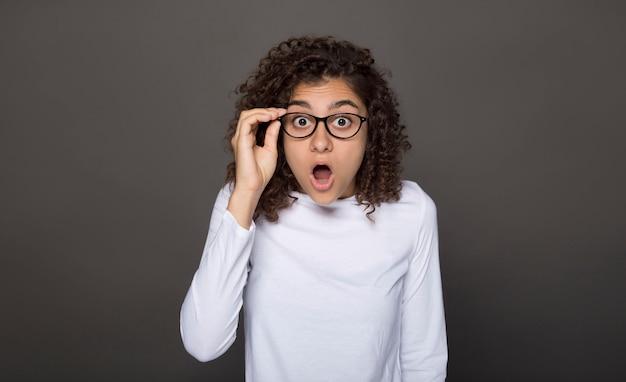 Choque en la cara de la niña con gafas. sorpresa loca en una mujer joven en un negro.