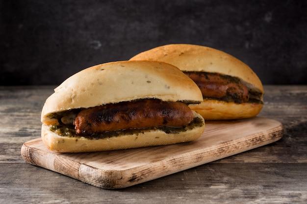 Choripan sandwich tradicional argentino con salsa de chorizo y chimichurri en mesa de madera