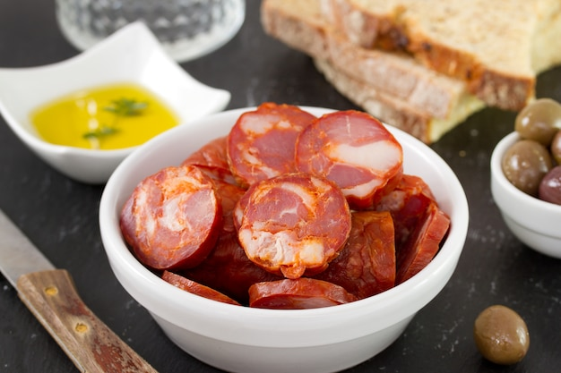 Chorizo en bol con aceite y pan