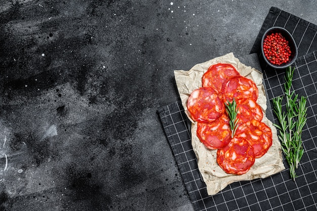 Chorizo de salami tradicional. fondo negro. vista superior. espacio para texto